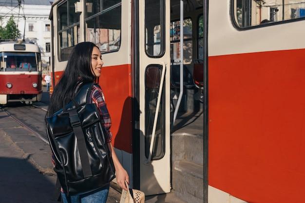 バックパックを運ぶとトランプのドアの前に帽子立っているを持つ女性の笑みを浮かべてください。 無料写真