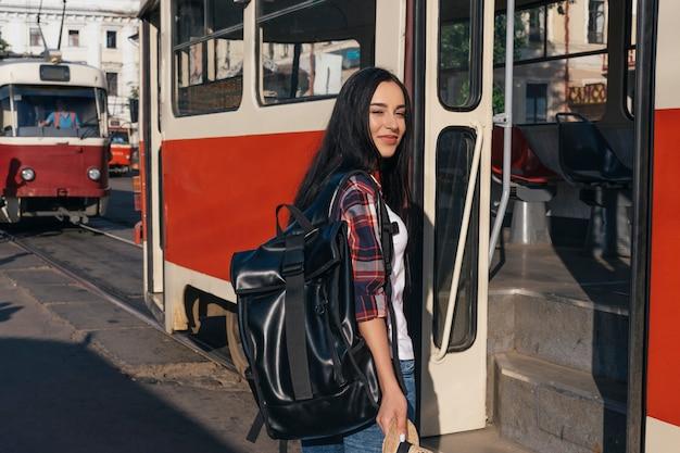路上の路面電車の近くに立ってバックパックを運ぶ笑顔の女性 無料写真
