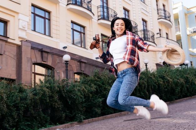 帽子とカメラを持って通りにジャンプ美しい若い女性 無料写真