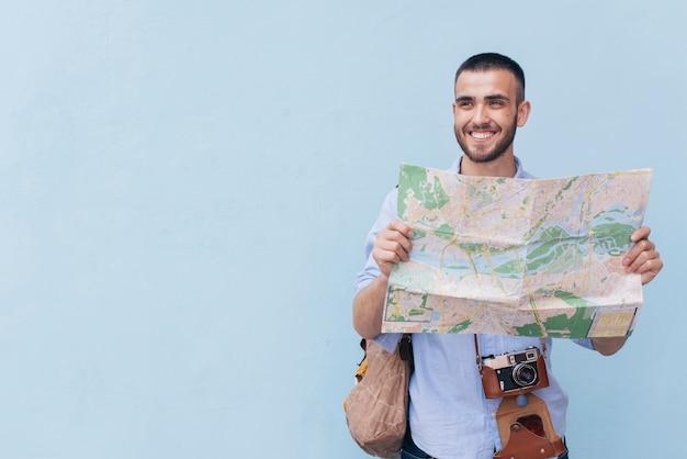 マップを保持していると青い背景に対して離れて立っているを見て笑顔の旅行写真家 無料写真