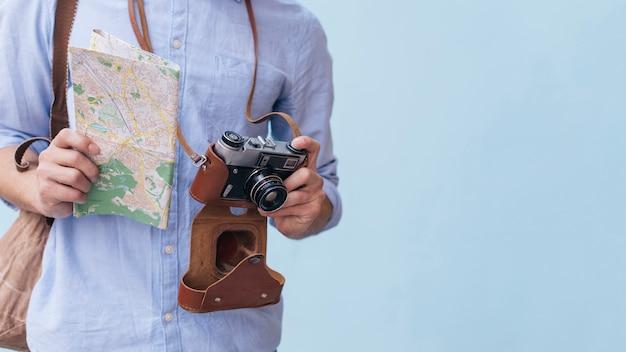 カメラと青い背景に立っているマップを保持している男性の旅行者写真家の中央部 無料写真