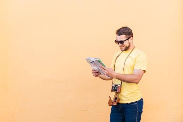 桃の背景に地図を読んで彼の首の周りのカメラを持つ若い男性旅行者の写真家 無料写真