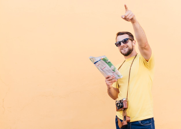 ハンサムな若い旅行者写真家白い地図を押しながら彼の首の周りの白いカメラ 無料写真