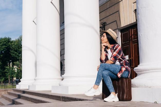 屋外を離れて見て荷物バッグに座っている美しい女性 無料写真