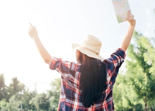 Вид сзади женщина держит карту и поднял руку Бесплатные Фотографии