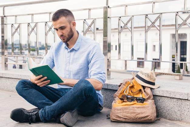 屋外で手すりの近くに座って本を読んで深刻な若い男 無料写真