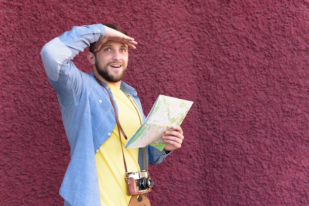Улыбающийся мужчина путешественник фотограф, прикрывая глаза, держа карту на фоне текстурированной стены Бесплатные Фотографии