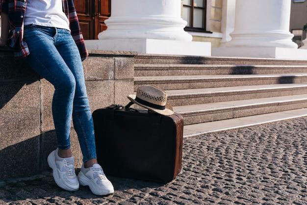 彼女の荷物の袋と帽子の近くの壁にもたれて女性の低いセクション 無料写真