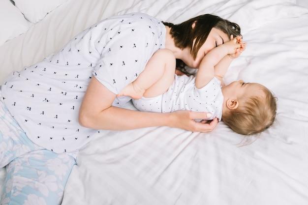 ベッドの中で赤ちゃんと母親 無料写真