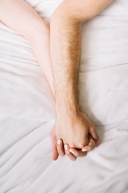 ベッドで手を繋いでいるカップルのクローズアップ 無料写真