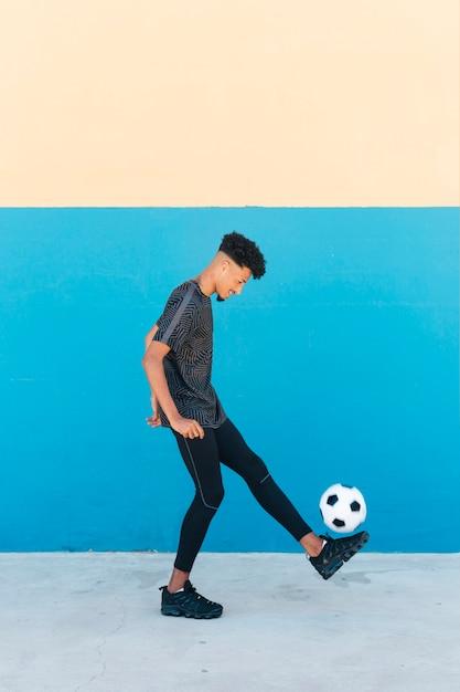 陽気なスポーツマンの壁の近くのサッカーボールを蹴る 無料写真