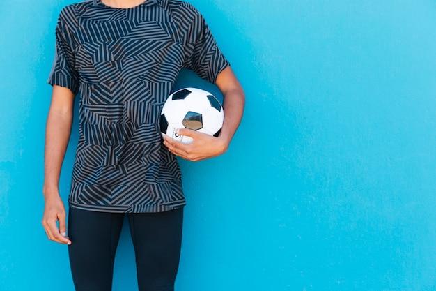 青い背景にサッカーを持つ男性の作物 無料写真