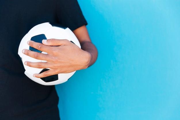 壁の近くにサッカーボールを保持している腕の作物 無料写真