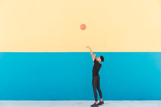 ボールを投げるエスニックバスケットボール選手 無料写真