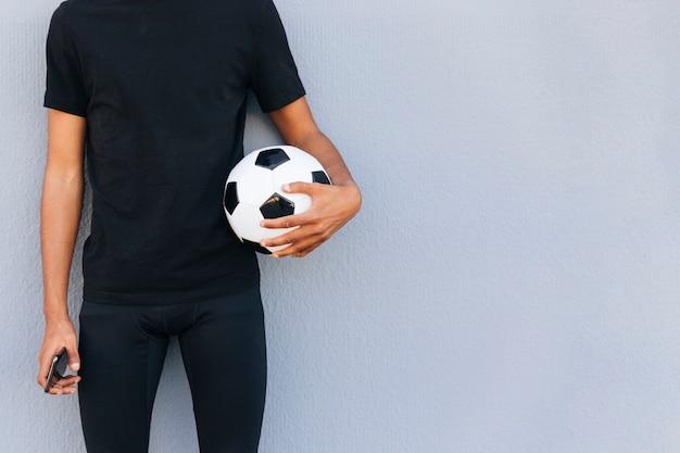 サッカーと電話で立っている陽気な人 無料写真