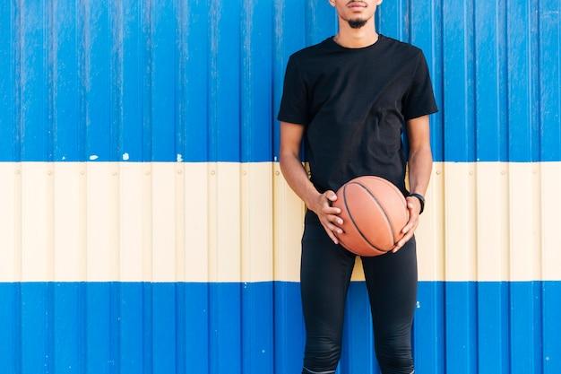 バスケットボールを保持している壁に立っている顔のない運動男性 無料写真