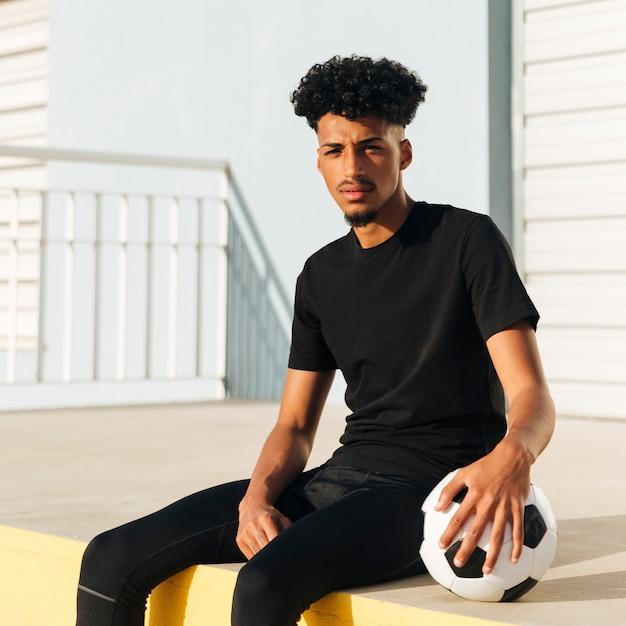サッカーボールで座っている民族の運動男 無料写真