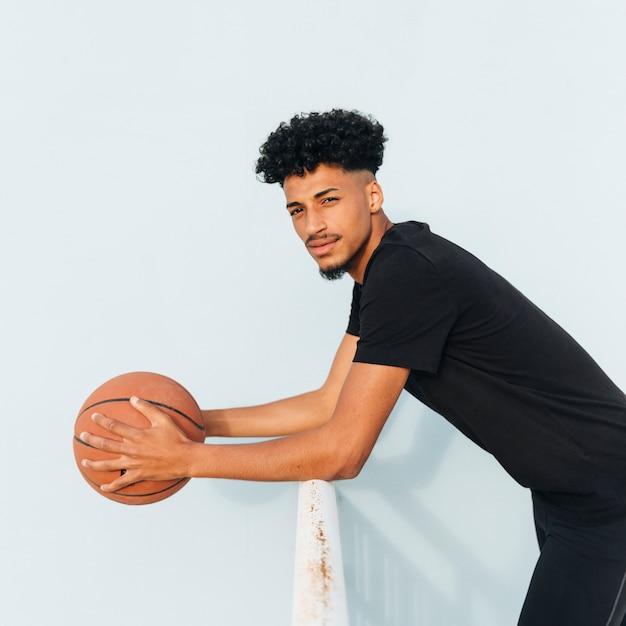 手すりにもたれてバスケットボールと黒のスポーツマン 無料写真