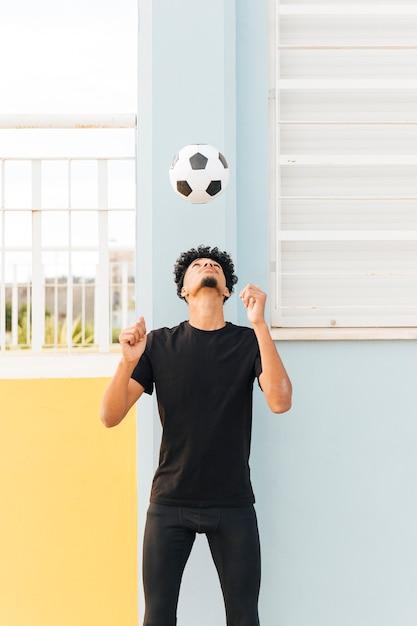 Футболист бросает мяч на крыльце Бесплатные Фотографии