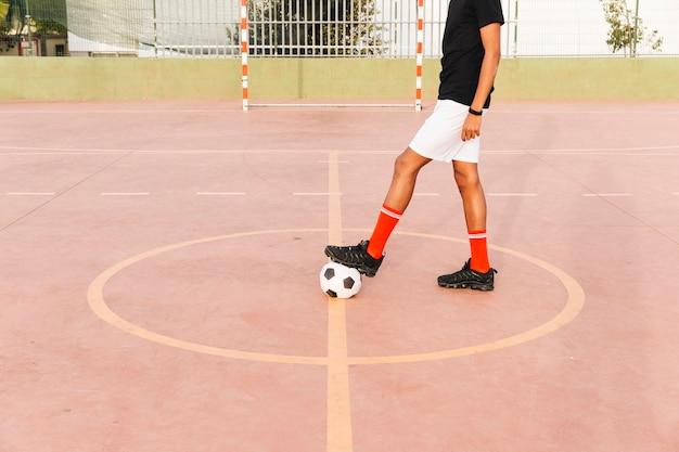 スタジアムでサッカーボールのフットボール選手の足 無料写真