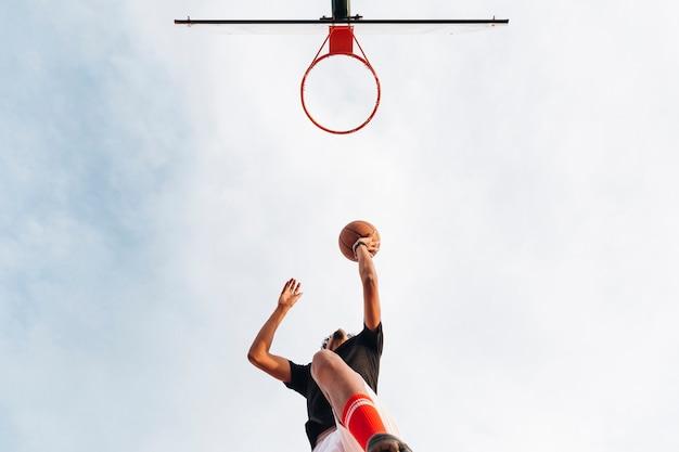 バスケットボールをネットに投げ運動の男 無料写真