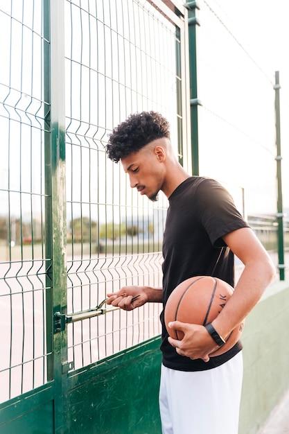 民族の若い男がバスケットボールのコートを開く 無料写真