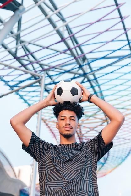 金属構造に対して頭の上にサッカーを保持している男性のスポーツマン 無料写真