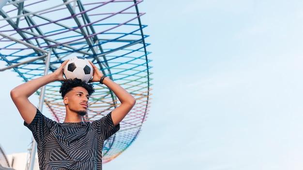 青い空を背景に頭の上にサッカーボールを保持しているオスの運動選手 無料写真