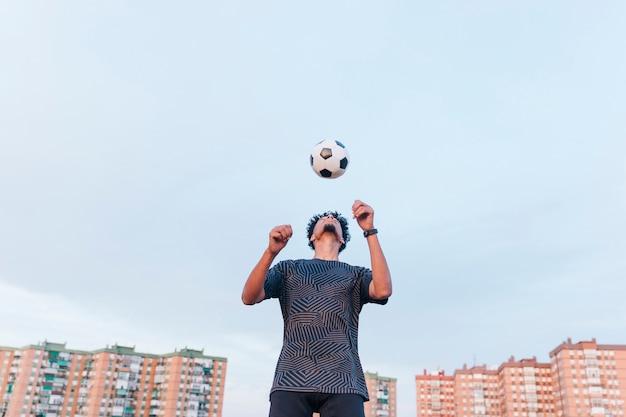 青い空を背景にサッカーボールで運動する男性のスポーツマン 無料写真