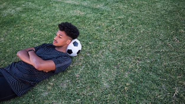Футболист лежа и имея паузу на футбольном поле Бесплатные Фотографии