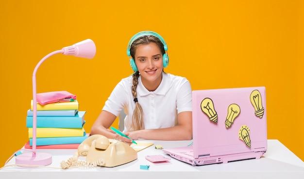Школьница на столе с ноутбуком в стиле мемфис Бесплатные Фотографии