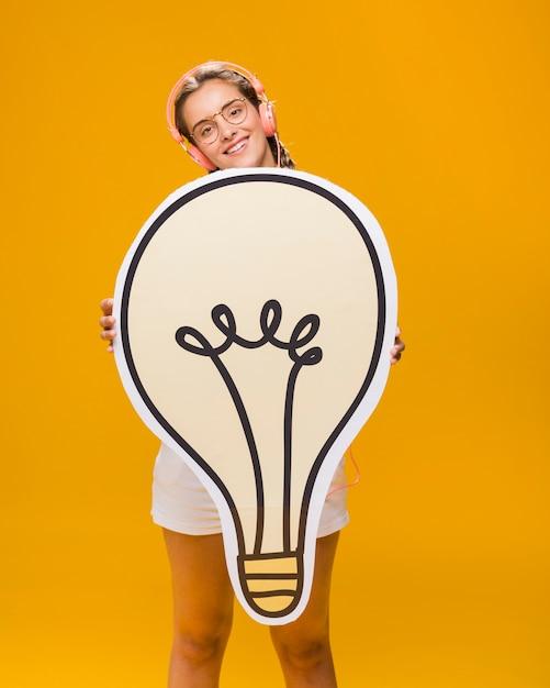 大きな電球を持つ女子高生の肖像画 無料写真