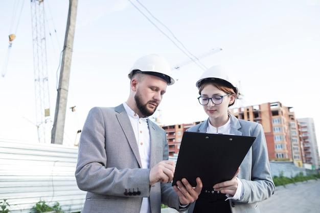 クリップボードを見てハード帽子をかぶっている若い女性と男性の建築家 無料写真