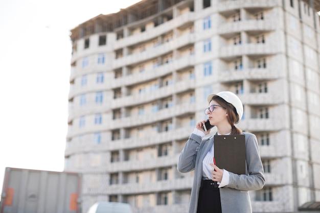 建設現場でクリップボードを保持している携帯電話で話しているプロの若い女性建築家 無料写真