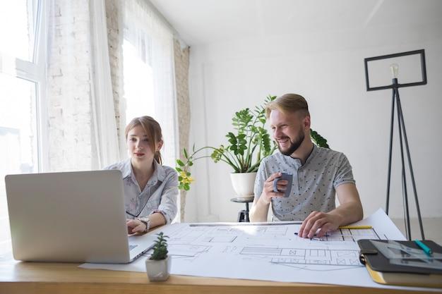 笑みを浮かべて男のオフィスで彼の女性の同僚を使用してラップトップを見てコーヒーカップを保持 無料写真