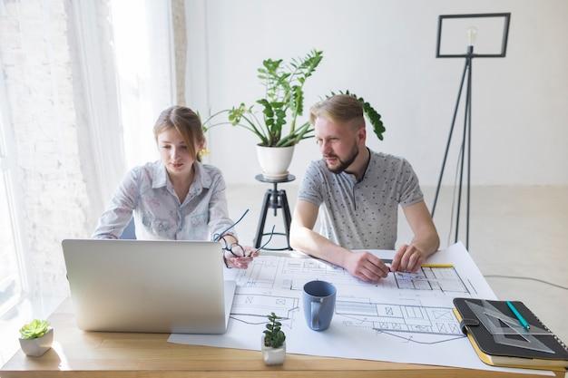 若い男が職場で彼女の同僚を使用してラップトップを見て 無料写真