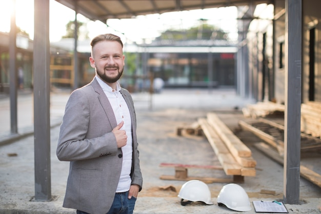 カメラを見てジェスチャーを親指を示す笑みを浮かべて若い建築家男の肖像 無料写真
