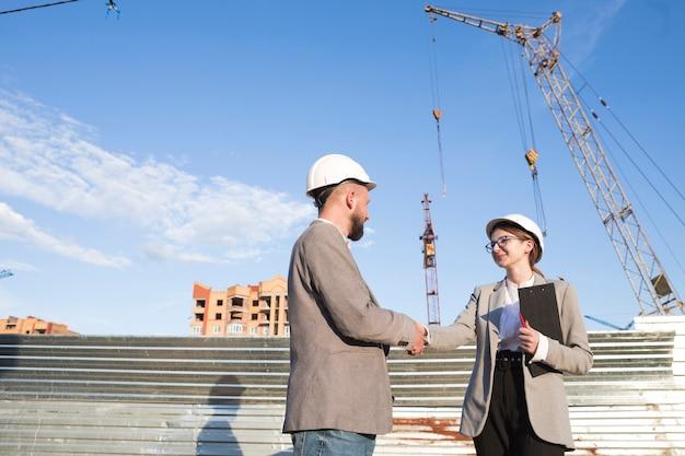 Два профессиональных инженера пожимают руку на строительной площадке Бесплатные Фотографии