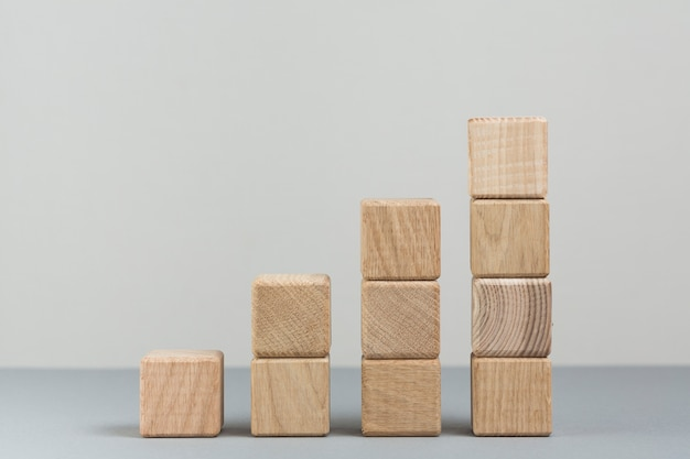 灰色の背景上の増加する木製のブロックのスタック 無料写真