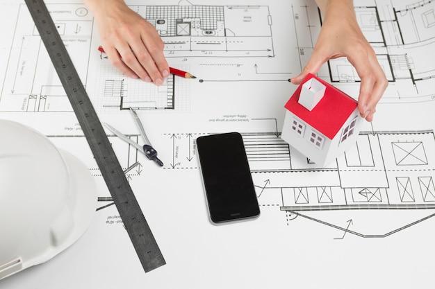 Женская рука держит модель дома над планом в офисе Бесплатные Фотографии