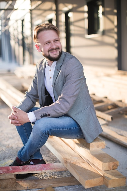 Улыбающийся молодой человек, сидя на деревянной доске на открытом воздухе Бесплатные Фотографии