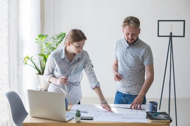 若い女と男のオフィスで青写真に一緒に取り組んで 無料写真