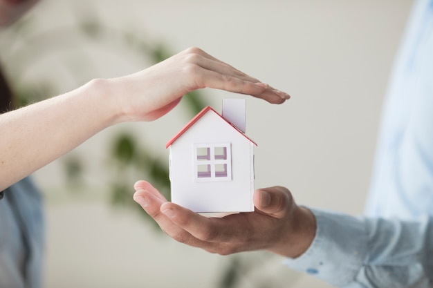 小さな家のモデルを保護する手のクローズアップ 無料写真