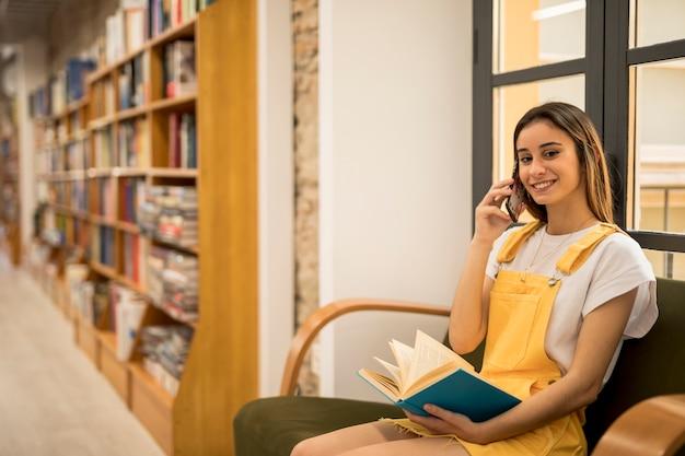 電話で話していると青い本を持って笑顔の若い女性 無料写真