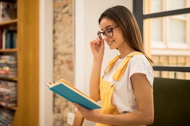 魅力的な若い女性は図書館で本を読んで 無料写真