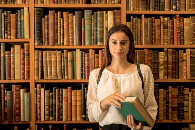 本棚に対してカメラを見て自信を持って女性 無料写真