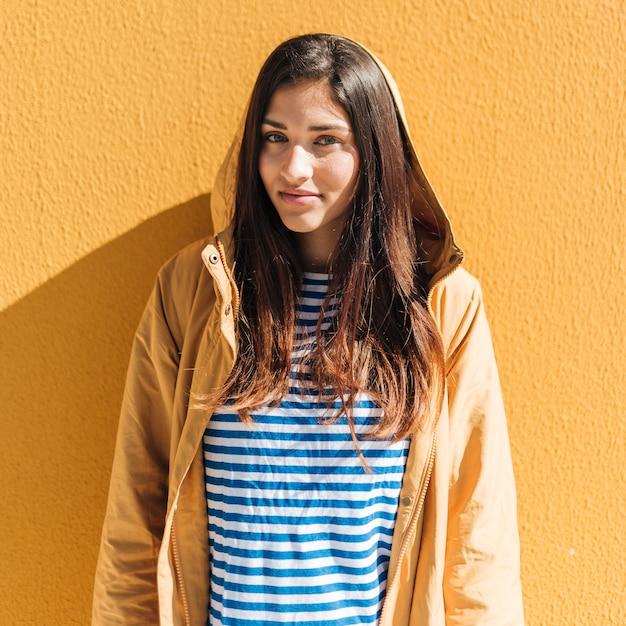 黄色の壁に対して立っている美しい女性 無料写真