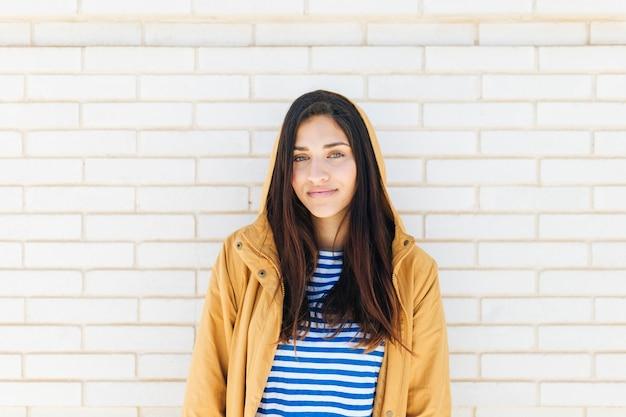 レンガの壁に立っているジャケットを着て幸せな女 無料写真