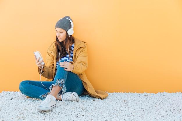 Женщина сидит на ковре с помощью смартфона, слушая музыку в наушниках Бесплатные Фотографии