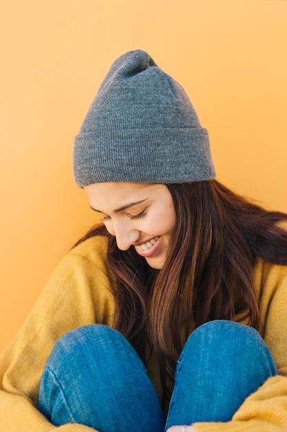 黄色の背景に対して座っている帽子をかぶっている内気な女性 無料写真